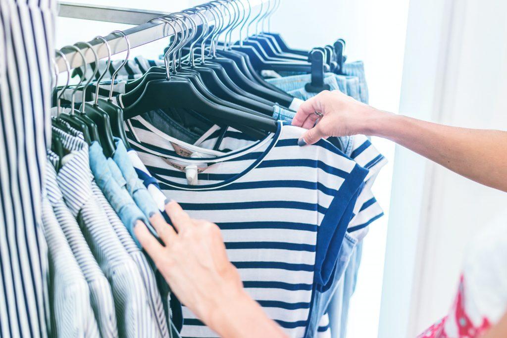 Nainen tutkii vaatteita. Kuva: Artem Beliaikin/Unsplash.