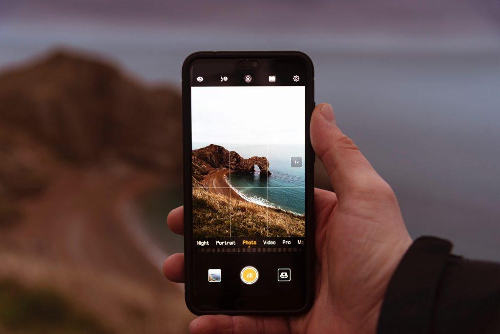Kuvassa mies pitää mobiilipuhelinta kädessään. Kuva: Oscar Sutton / Unsplash