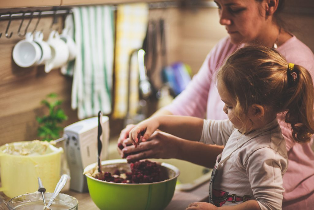 Tyttö ja äiti sekoittaa marjoja