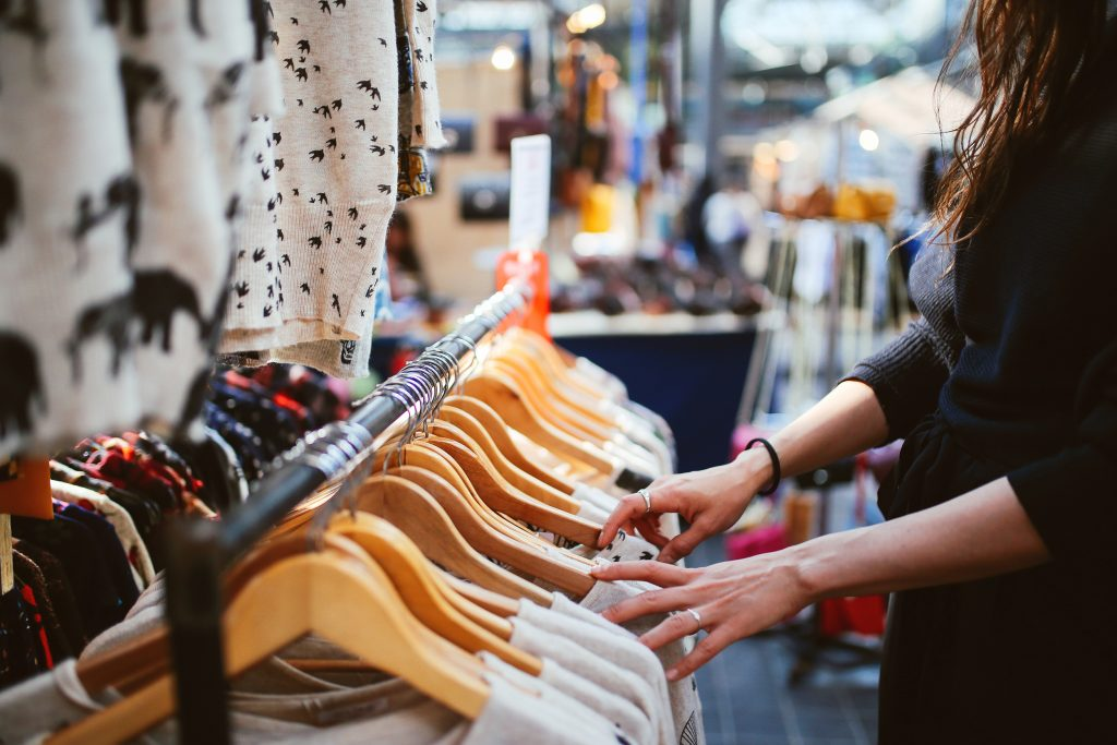 Nainen katselee vaatekaupassa henkareissa roikkuvia vaatteita.