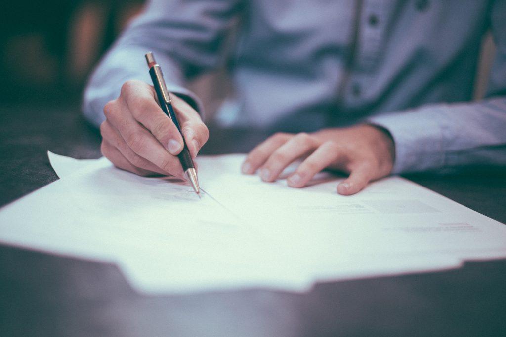 Mies allekirjoittaa sopimuksen