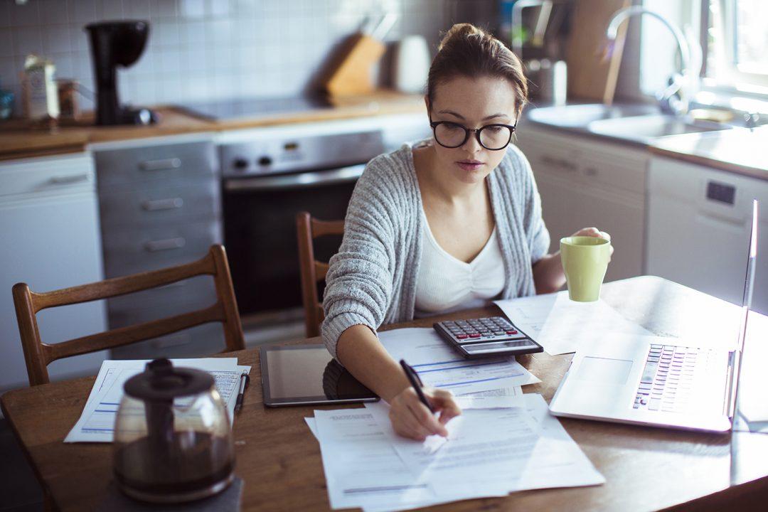 Nainen istuu keittiönpöydän ääressä kahvikuppi kädessään ja kirjoittaa paperille. Pöydällä on kannettava tietokone, taskulaskin ja kahvipannu.