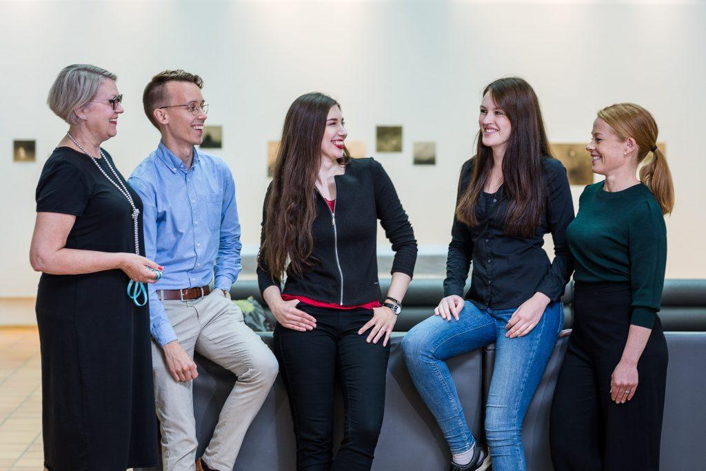 Mies ja neljä naista seisovat sohvan edessä, katsovat toisiinsa ja hymyilevät.