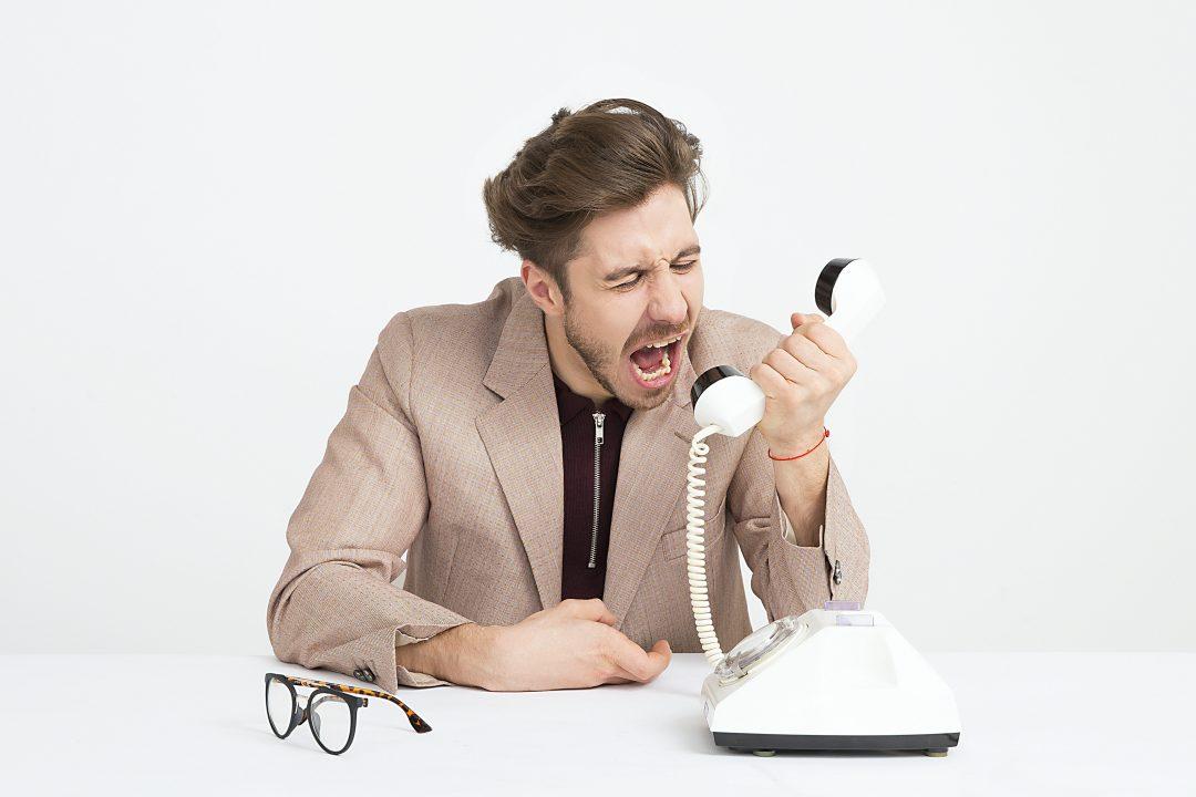 Mies istuu pöydän ääressä ja huutaa valkoiseen lankapuhelimeen.