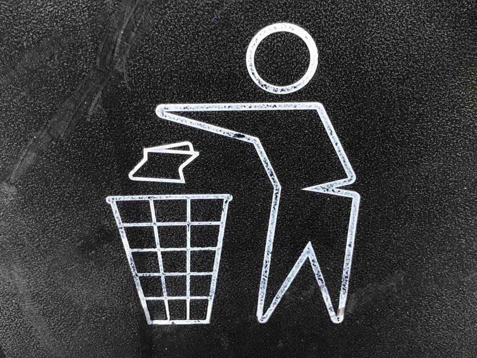 Piirroskuva ihmishahmosta, joka laittaa roskan roskakoriin. Mustavalkokuva.