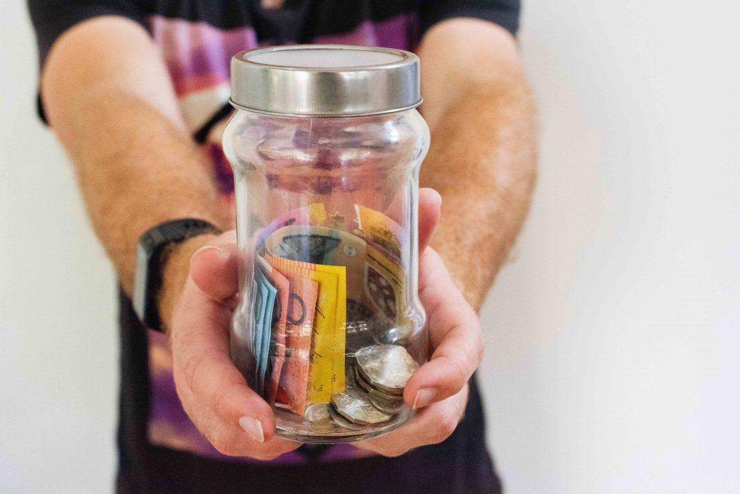 Mies pitelee lasipurkkia, jonka sisällä on rahaa. Kuva: Melissa Walker-Horn/Unsplash.