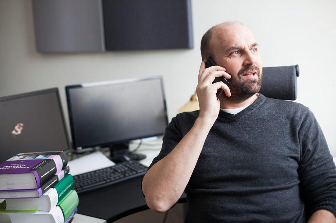 Mies istuu työpöydän ääressä ja puhuu puhelimeen.