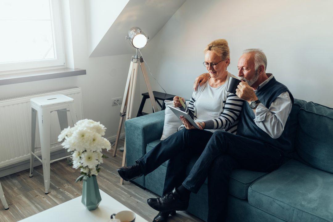 Kaksi vanhempaa ihmistä istuu sohvalla ja katsoo tablettia.