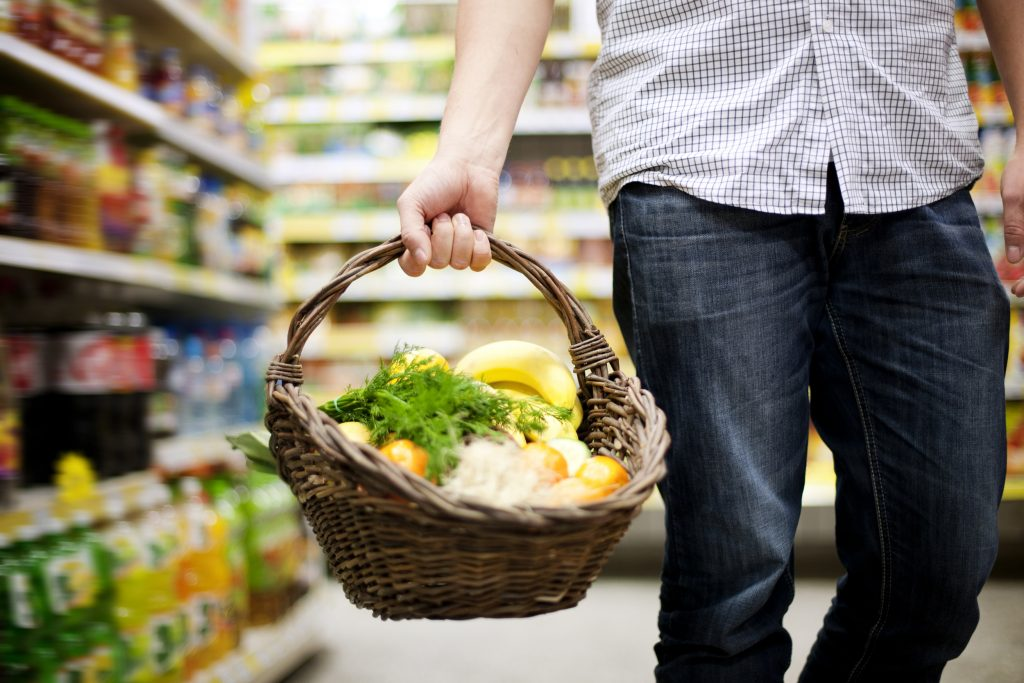 Kuvituskuvassa mies asioi kaupassa ja kantaa punottua ostoskoria, jossa on vihanneksia. Miehen kasvot eivät näy.