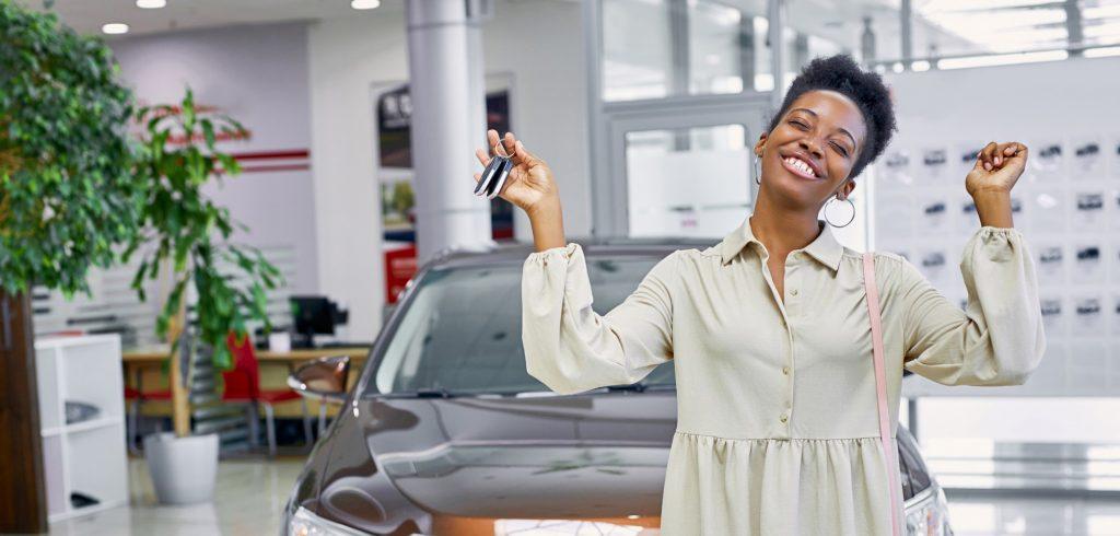 Kuvituskuvassa nuori tummaihoinen nainen iloitsee auton avaimet kädessään. Taustalla auto ja autoliike.